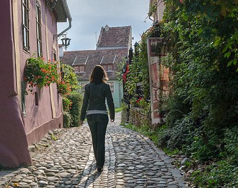 Woman Walking on a Cobblestone Street