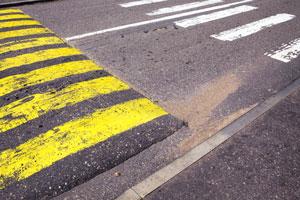 pedestrian crosswalk and yellow-striped speed bump